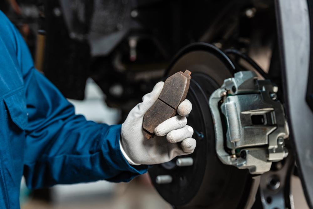 car mechanic looking at a brake pad